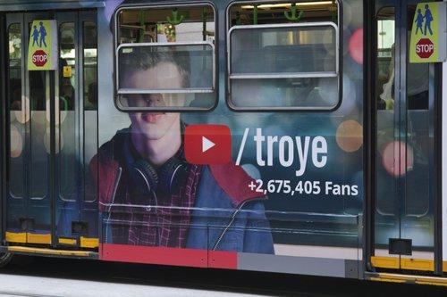 Eyeless pretty boy on the side of a tram