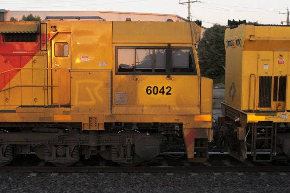'QR' logo drawn into the grime of Aurizon locomotive 6042