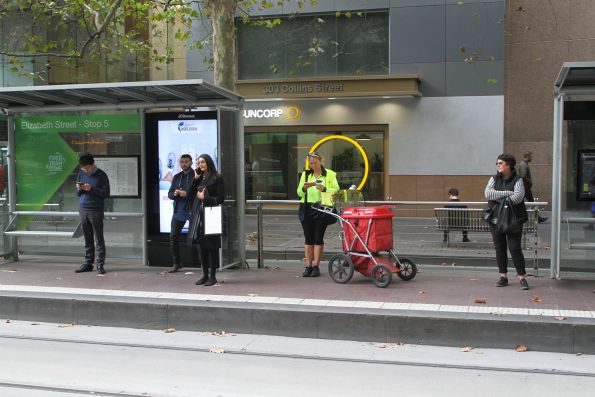 Australia Post postie waiting for a tram down Collins Street