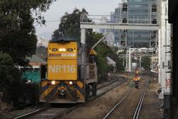 NR116 passes the flagman protecting a worksite at West Footscray