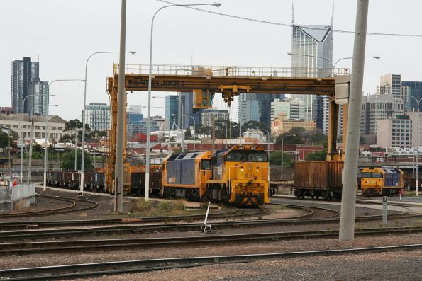 XR551 and a BL class stand under the overhead crane at the Melbourne Steel Terminal, with another BL class hiding in the storage roads