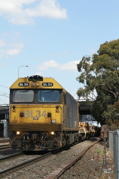 BL34 departs West Footscray with a rake of empty coil steel wagons from Tottenham Yard