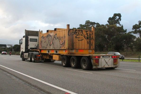Semi trailer carries a single 'butterbox' steel container citybound on the Monash Freeway