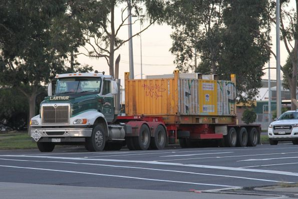 Semi trailer carries a single 'butterbox' steel container along Footscray Road bound for the Melbourne Freight Terminal