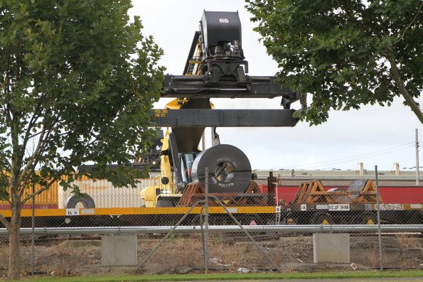 Reach stacker transferring coil steel from standard to broad gauge wagons at South Dynon
