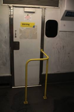 Fence around the cab door of Comeng 541M with Connex-era modified seating layout