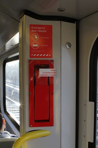 Plastic guard added over the emergency door release onboard a Siemens train