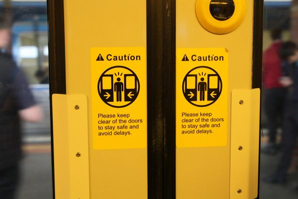 'Please keep clear of the doors to stay safe and avoid delays' stickers on the doors of a Siemens train