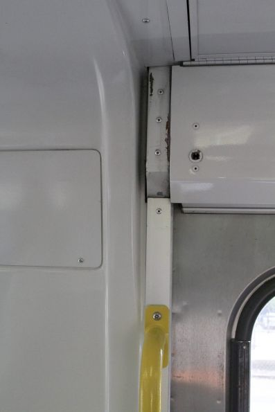 Bodgy looking gap onboard an EDI Comeng train where the door windbreaks used to attach to the saloon walls