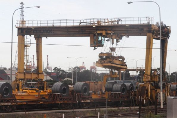 Mi Jack crane transferring coil steel between broad and standard gauge wagons at the Melbourne Steel Terminal