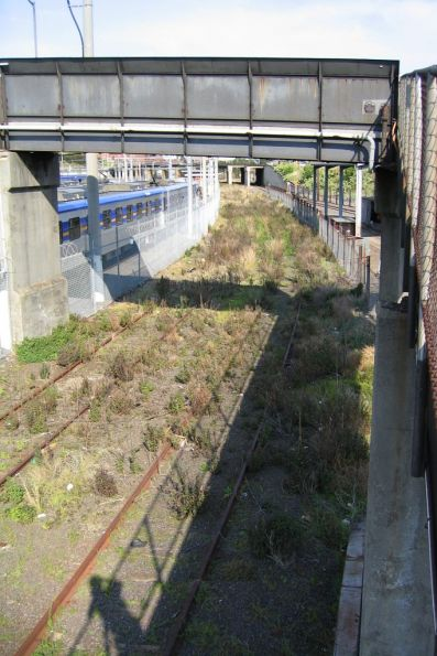 Outside Goods Lines head beneath the yard footbridge at North Melbourne