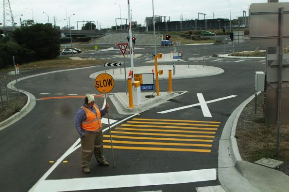 Traffic controllers stop traffic from crossing an unprotected level crossing that leads into 'E' Gate