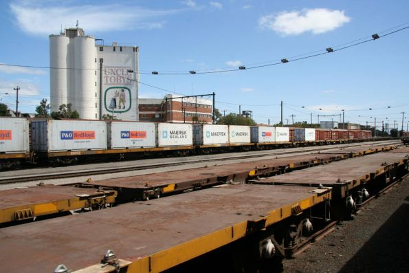 Stored flat wagons, along with loaded container for somewhere