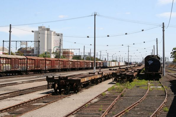 Stored louvred vans, tank wagons and container flats at the up end of the yard