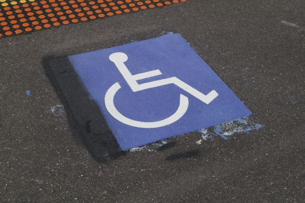 Three attempts at a wheelchair symbol on the platform