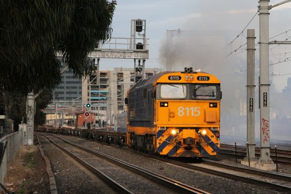 8115 leads a rake of empty container wagons past Middle Footscray station on the down