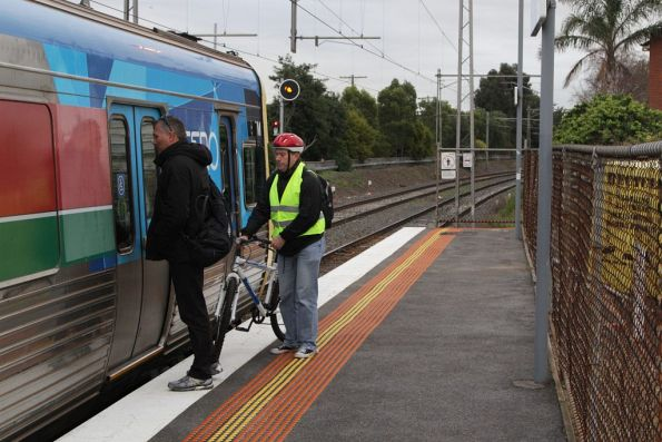 Cyclist loading their bike into the last carriage of the train