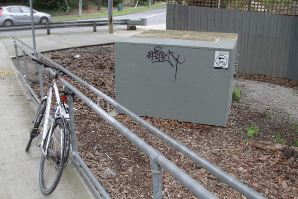 Seldom used bike locker at Laburnum station, with another bike chained to a nearby railing