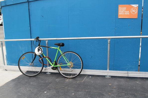 Bike chained up beneath the 'Please do not park your bikes here' sign