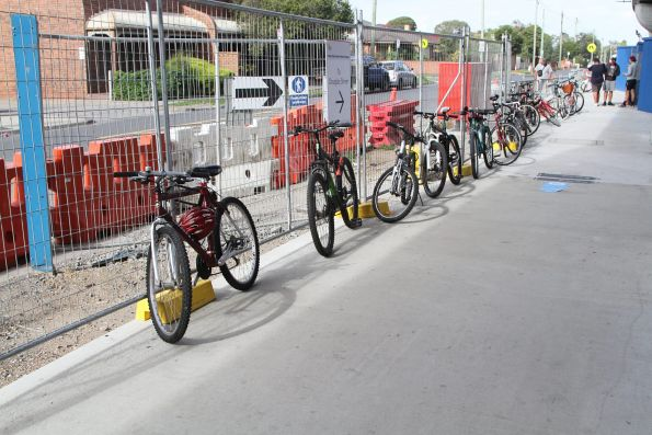Bikes chained up to fences in the forecourt of the new Noble Park station