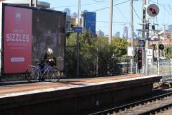 Cyclist at Kensington oblivious to the 'no bikes at front door' signage on the platform