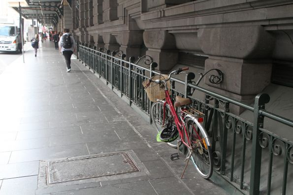 Bike chained up to the fence at Flinders Street Station