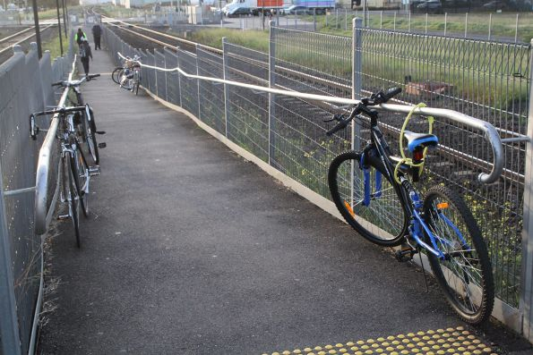 Bikes chained up along the railings leading to Deer Park station