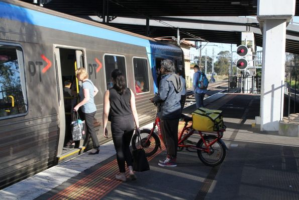 Food delivery rider takes an e-bike aboard a suburban train