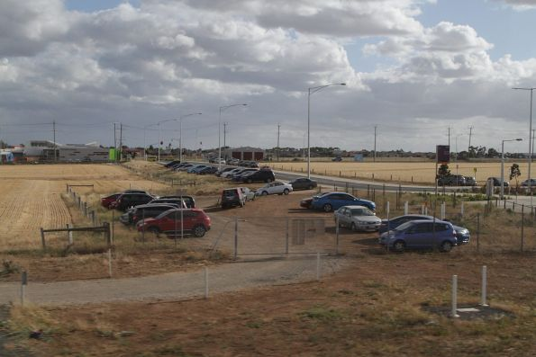 Cars parked in the dirt on the south side of Tarneit station