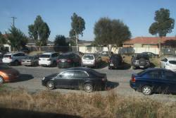Cars park beside the tracks at the city end of Keilor Plains station