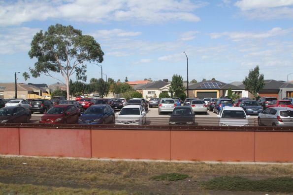 Gravel car park on the south side of Deer Park station full of cars