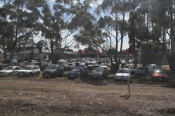 Ad hoc dirt car park on the north side of Melton station full of cars