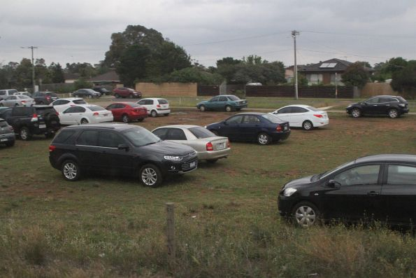 Cars parked on the dirt at Melton station