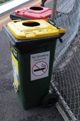 New 'No Smoking / Penalties apply' sign on a rubbish bin at a suburban railway station