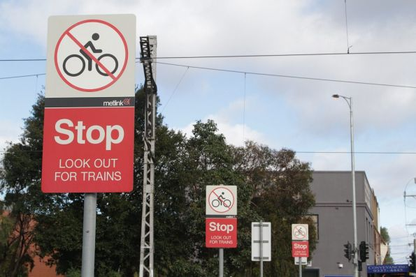 Metlink branded 'Stop / Look out for trains' signs at a level crossing