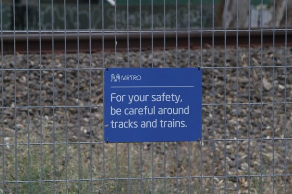 Metro 'For your safety, be careful around tracks and trains' sign affixed to a rail corridor fence