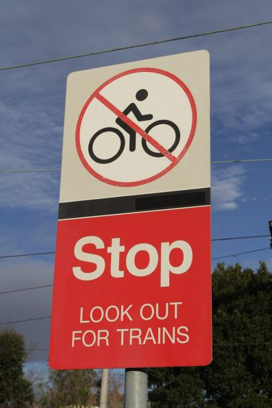 'Metlink' branding blacked out on warning signage at Essendon station
