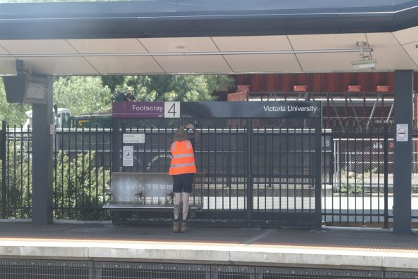 Removing the recently installed 'Victoria University' signage at Footscray station