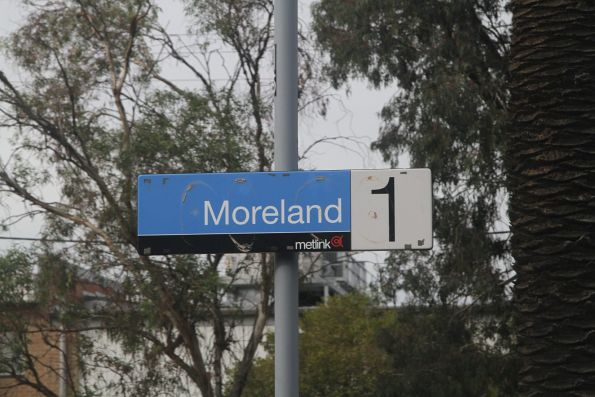 Metlink station sign exposed beneath the PTV coverplate at Moreland station