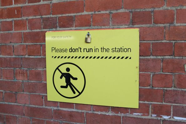 Fold down 'Please don't run in the station' sign in the subway at Oakleigh