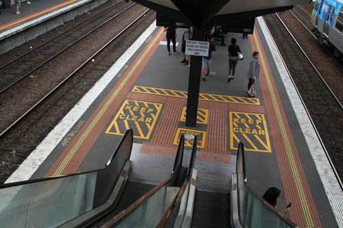 'For safety reasons please keep hatched area clear at all times' sign beneath the escalator at North Melbourne station
