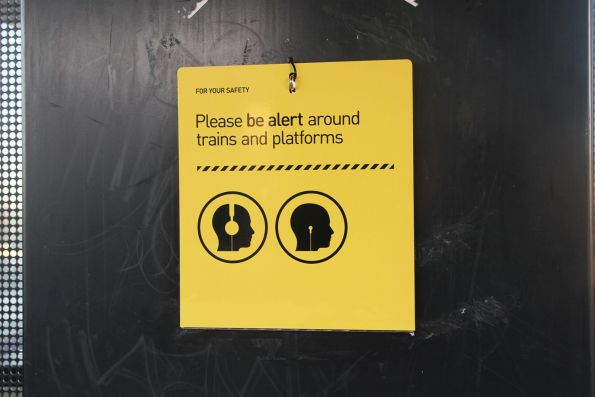 Fold down 'Please be alert around trains and platforms' sign at Sunshine station
