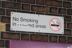 'No smoking in covered areas' sign, with a 'in all station' sticker over the top