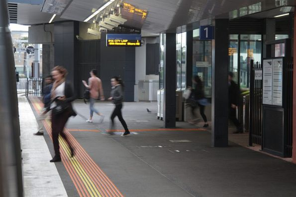 Passengers run for a waiting City Loop train at Footscray platform 1