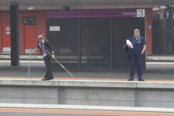 Metro staff at Footscray looking onto the tracks for a missing item