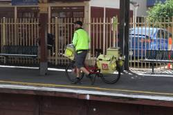 Australia Post postie leaves a train at Clifton Hill station