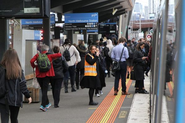 Metro staff on crowd control in morning peak at North Melbourne platform 5
