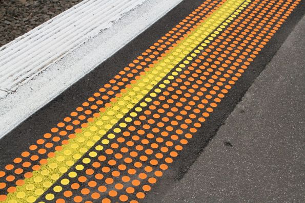 Painted yellow line beneath the tactile paving at Tottenham