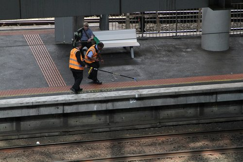 Metro Trains staff retrieve a mobile phone from the tracks with a long pickup claw