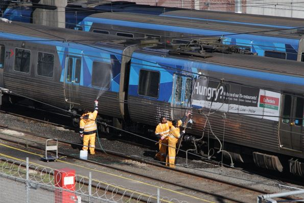 Washing down a Comeng train by hand at Melbourne Yard